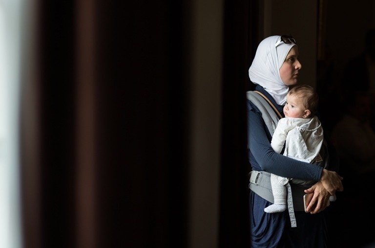 Hiba Tinawi, from Syria, holds her six-month-old daughter Judy during an event to welcome Syrian refugee families who have recently resettled in the city of Clarkston, Georgia. World Relief, an international NGO, is helping the newest arrivals resettle in the Atlanta region. (Branden Camp/Atlanta Journal-Constitution via AP)
