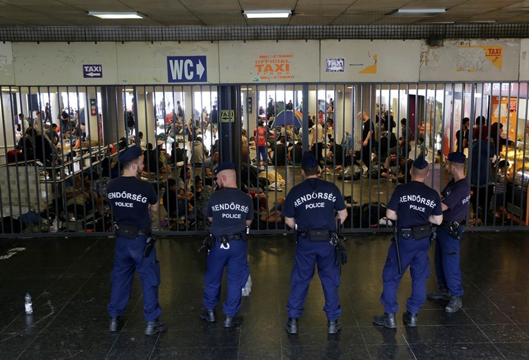 Hungarian policemen guard an entrance to Keleti railway station in Budapest as hundreds of migrants try to board trains to Germany. (AP/Petr David Josek)