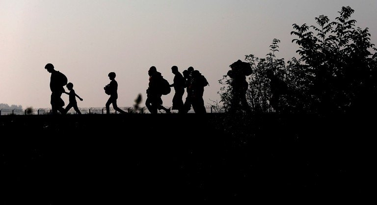 Migrants walk along the railway track after crossing the border between Serbia and Hungary on Sept. 13, 2015. (AP/Matthias Schrader)