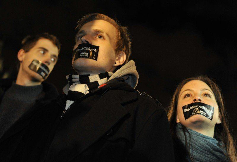 "Hungarian Amnesty International activists protest with taped mouth during a demonstration against the government's new media law in Budapest in 2011. The message, in Hungarian, reads ""We want press freedom!"" (AP/Bela Szandelszky)"