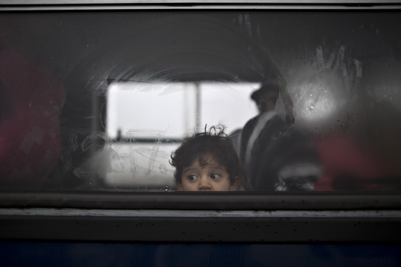 A Syrian refugee child looks out of a bus that will take him and his family to the center for asylum seekers in southern Hungary. (AP/Muhammed Muheisen)