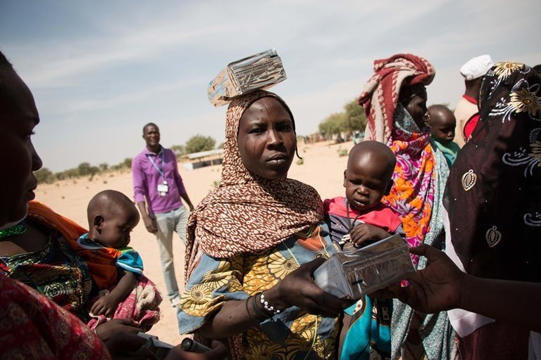 Women gather to collect aid at the Dar es Salaam refugee camp in Chad, close to the border to Niger. (Ashley Hamer)