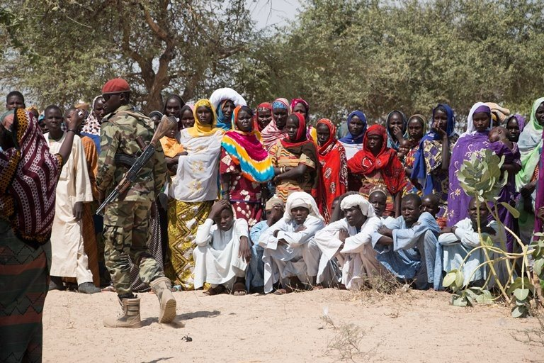 Chadian armed soldiers supervise aid distributions in the Lake Chad Basin. (Ashley Hamer)