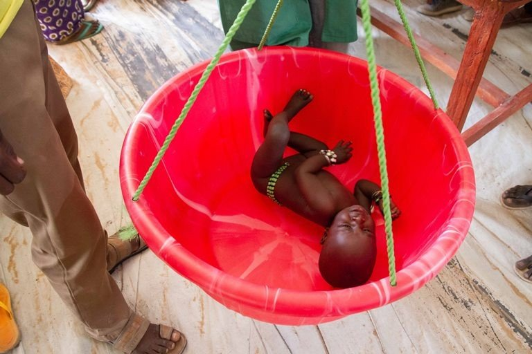 An infant is weighed at the Dar es Salaam refugee camp. (Ashley Hamer)
