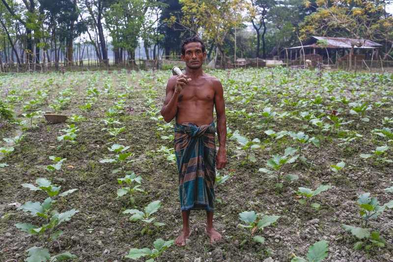 Amjad Miyah, 36, stands in a field in the island district of Bhola, Bangladesh. Three years after the sea swallowed his home on the Bangladeshi coast, he still has no property or possessions and survives only by tending others' fields in exchange for daily meals. (AP/Shahria Sharmin)