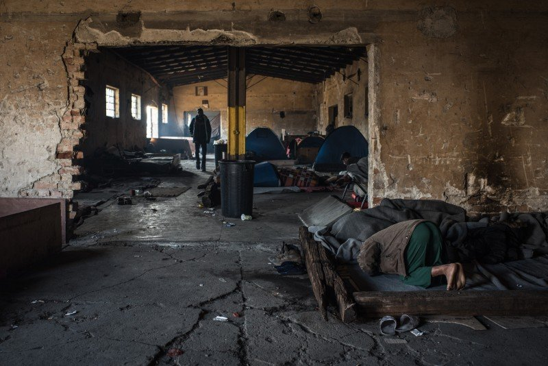 A man prays on his sleeping area inside one of the smaller buildings inside the abandoned train depot complex. (Diego Cupolo)