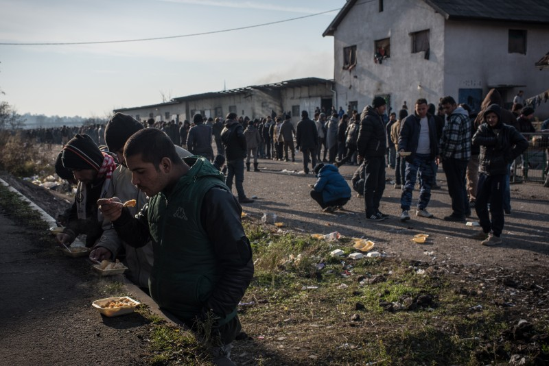 Asylum seekers line up to eat during the once-a-day food distribution organized by independent volunteers. The Serbian government has advised NGOs to stop providing aid to the warehouse inhabitants and encourage them to move out. (Diego Cupolo)