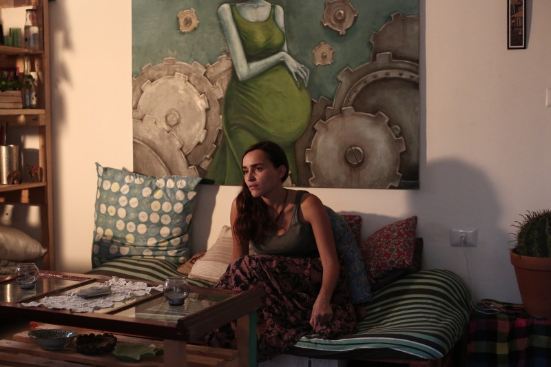 Artist Diala Brisly, from Damascus, Syria, sits in her living room, in front of her painting that she left behind then had sent to her in Lebanon. (Dylan Collins)
