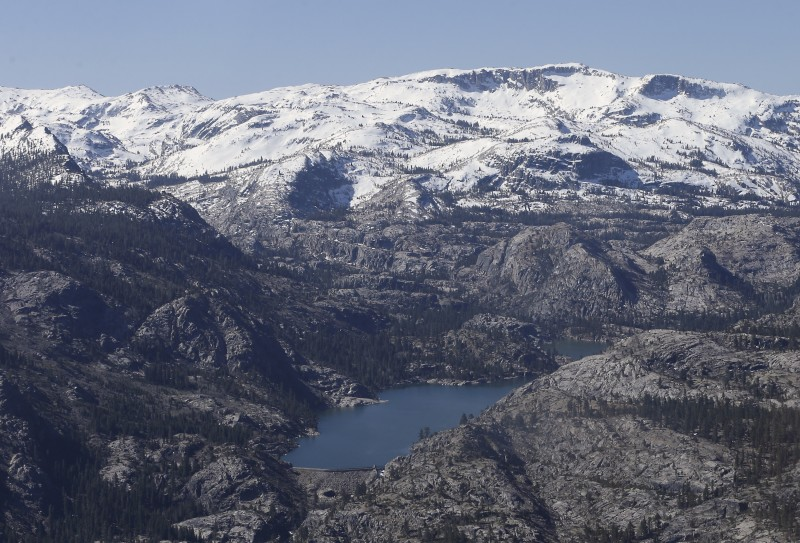 A Sierra Nevada reservoir in California is surrounded by barren ridges, usually covered in snow that time of year, during an aerial survey of the snowpack done by the California Department of Water Resources. (Rich Pedroncelli, Associated Press)