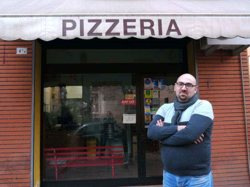 Hassan M. outside of his pizzeria in Bologna, Italy, which he has owned for 11 years. (Sean O'Neill)