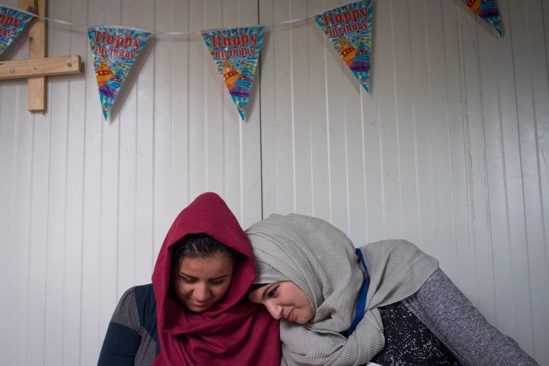 Hafsa Sabr (right) takes a moment to look at a photograph with a Kurdish refugee. Hafsa volunteers at the camp on a daily basis. (Razan Alzayani)