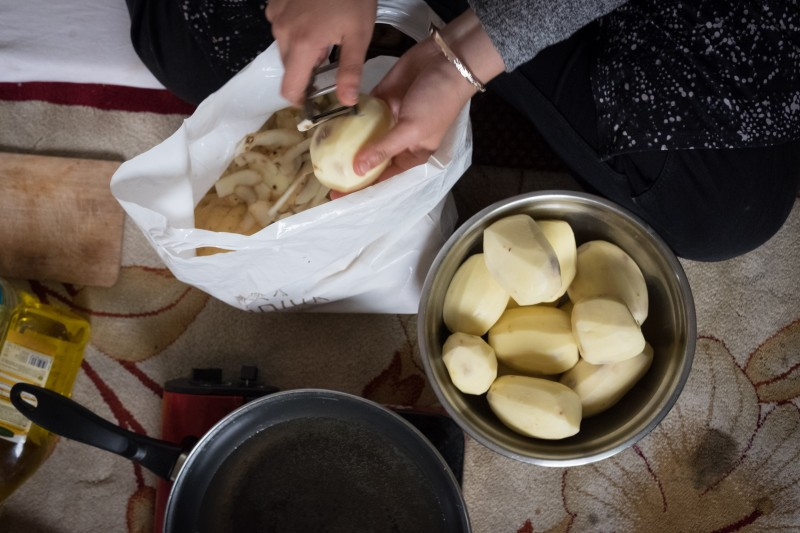 Refugees and local volunteers work together in the kitchen to prepare daily meals. Hafsa, a Dunkirk local, peels the potatoes. (Razan Alzayani)