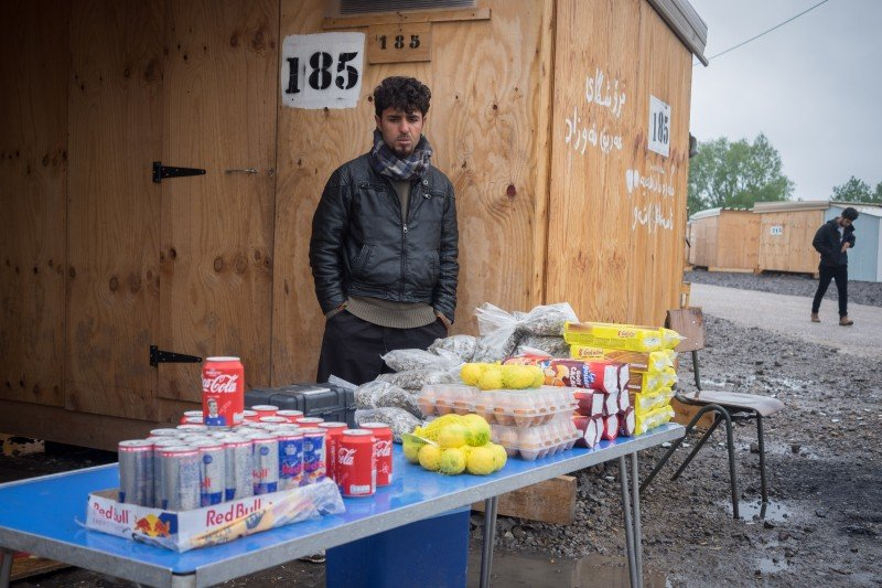An Iranian asylum seeker poses for a portrait with his produce. (Razan Alzayani)