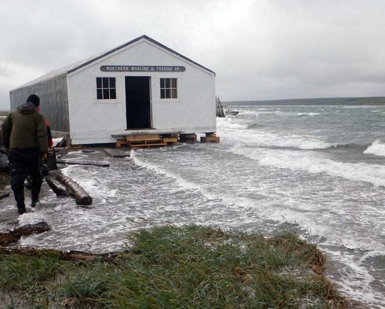 The ocean laps against a historic whaling building on Hershel Island. (Photo Courtesy the Government of Yukon)