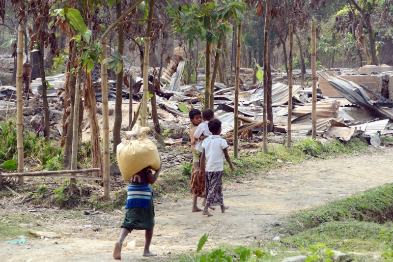Local residents walk past burned houses in Maungdaw in Myanmar's Rakhine State, which has a large Muslim Rohingya population. They claim soldiers from the country's armed forces burned a village in October. A number of Rohingya women there also claim to have been raped. (Kyodo)