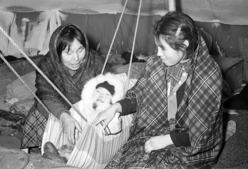 Two Inuit women in a tent with a baby, near Inukjuak, Quebec, in 1947-1948. (Richard Harrington/Library and Archives Canada/PA-147312)