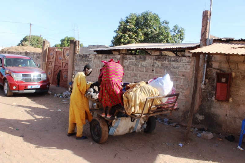 A Gambian man helps his mother onto a donkey cart as they leave a Senegalese border town and head back to their home in Gambia. (Sanna Camara).