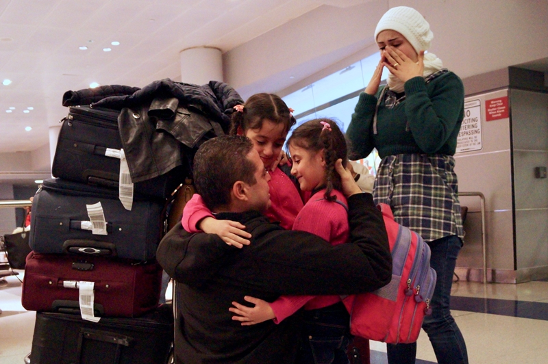 Fadi Kassar hugs his daughters as his wife Razan looks on after the family was reunited at John F. Kennedy International airport in New York City on February 2, 2017. (Bill Swersey/HIAS.org)