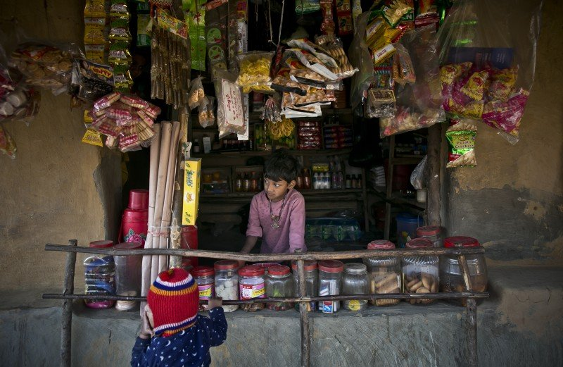 A young boy works at a shop in Kutapalong. (Allison Joyce/Koan Collective)