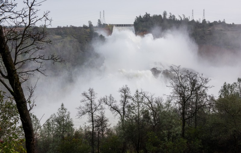 A huge spray cloud hangs over the Oroville Spillway as the California Department of Water Resources released 100,000 cubic feet per second (cfs) from the damage spillway to decrease the lake level by 50 feet to handle the next round of storms expected this week. Photo taken February 13, 2017. (Kelly M. Grow/ California Department of Water Resources)