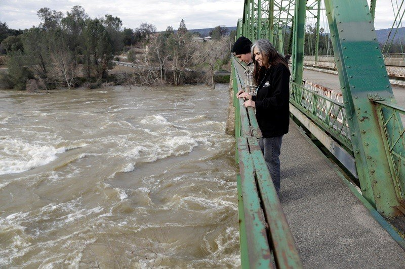 Marcie Peterson, center right, watches the gushing waters from the Feather River next to her son Robert Baltierra, Feb. 15, 2017, in Oroville, Calif. A levee setback project was recently completed on the Feather River to help reduce pressure on levees and flood danger to urban areas. (Marcio Jose Sanchez, AP)