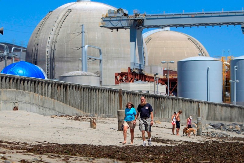 Beach-goers walking on the sand near the San Onofre nuclear power plant in San Clemente, Calif. The nuclear plant is now closed but a nonprofit wants to turn the facility into a solar-powered desalination plant. (AP, Lenny Ignelzi)