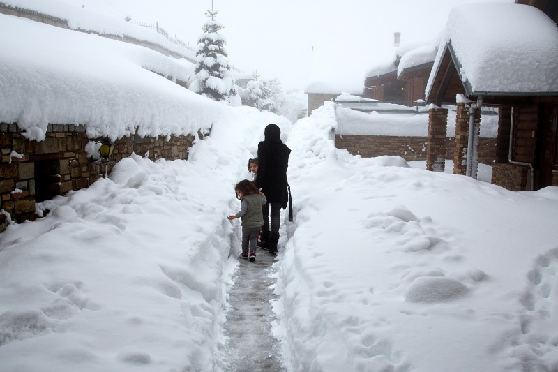 Syrian refugees in the deep snow at a ski chalet in the Greek mountains above Grevena. (Nikos Pilos)