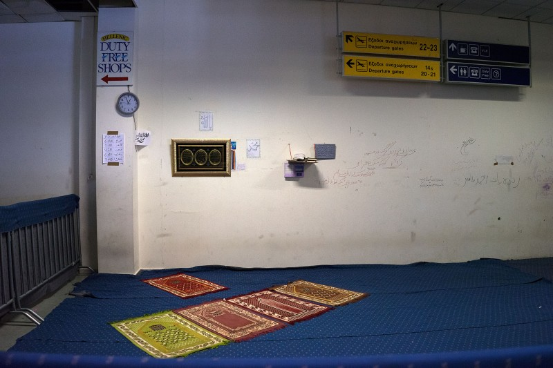 Prayer mats under the old Duty Free signs at the former Athens airport, now a refugee camp. (Nikos Pilos)