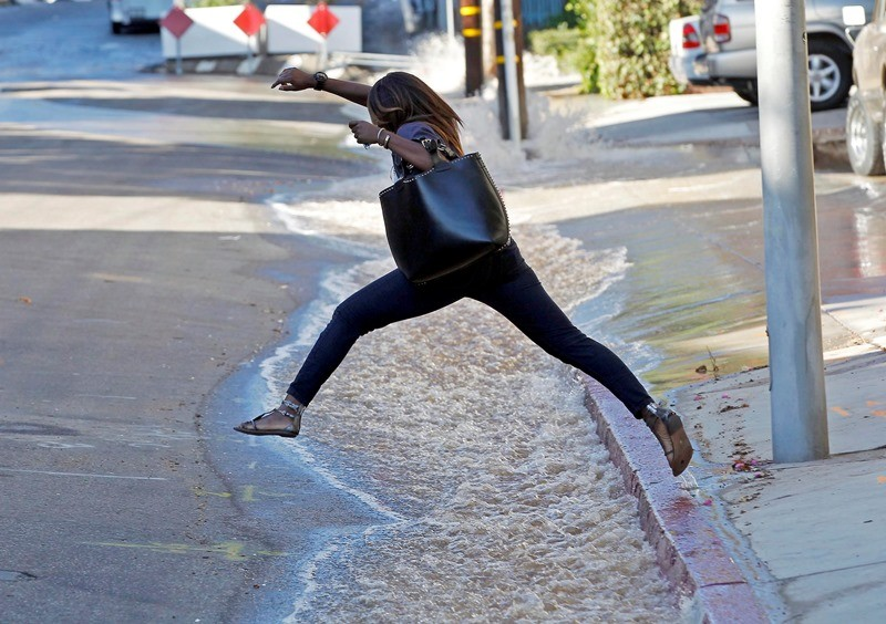 A woman leaps over water flooding a side street after a water main break sent churning, muddy water down Sunset Boulevard in West Hollywood, Calif., on Sept. 26, 2014. From October 2017 large water utilities in California will have to file audits of water loss in their distribution lines. (Nick Ut, AP)