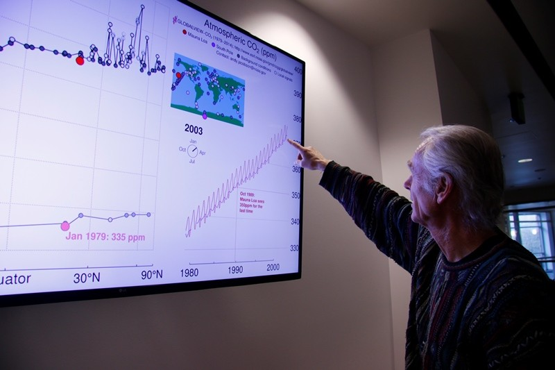 Pieter Tans points to a looping graphic in the basement of Boulder's NOAA office that shows the history of atmospheric carbon dioxide from 800,000 years ago until January 2016. (Gloria Dickie)