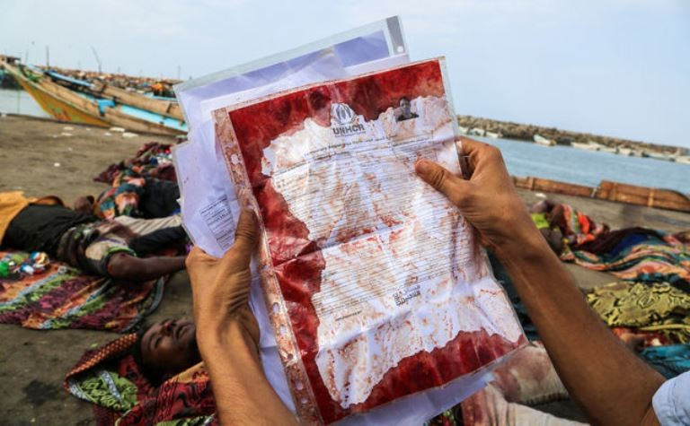 A man holds the UNHCR temporary registration document covered in blood from a refugee killed off the coast of Yemen on March 17, 2016. (AFP PHOTO / STR)