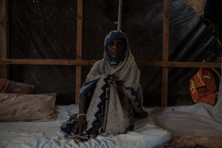 Madinah sits in her tent in Markazi refugee camp. (Emilienne Malfatto)