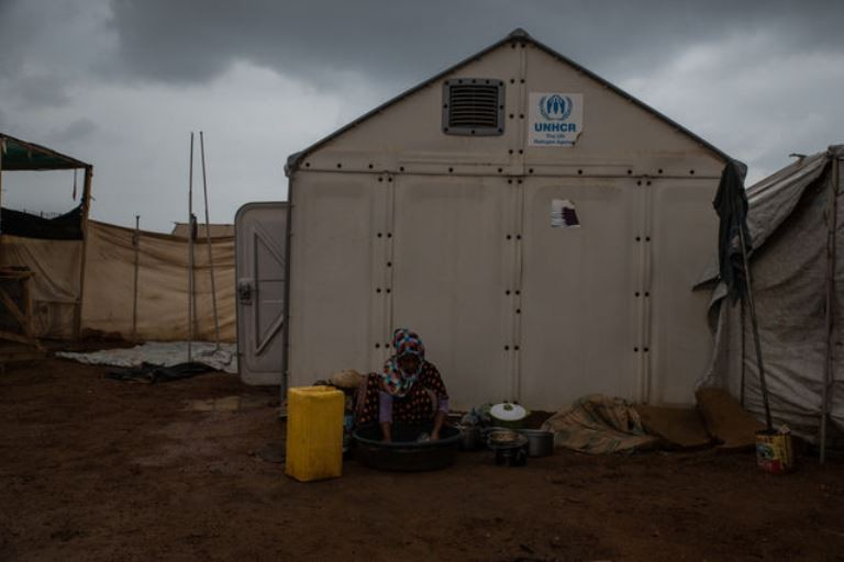 A young Yemeni refugee washes dishes outside her house in Markazi refugee camp. (Emilienne Malfatto)