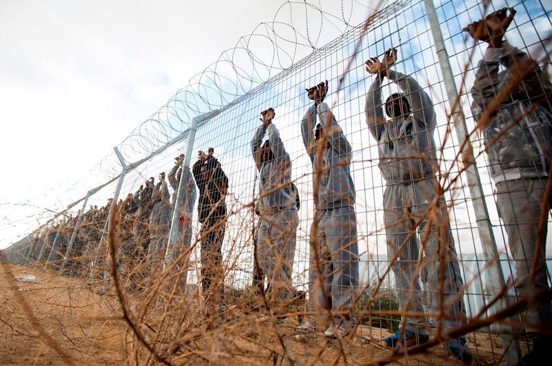 African asylum seekers lean at the fence of the Holot detention centre in Israel's southern Negev Desert, on February 17, 2014. (AFP/JACK GUEZ)