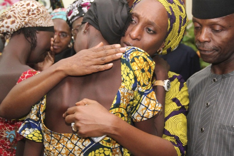 Nigerian Vice President Yemi Osinbajo (R) looks Dolapo Osinbajo, center, the wife of Nigerian Vice President Yemi Osinbajo, comforts one of the 21 Chibok girls who were freed in October 2016. (AFP/Philip Ojisua)