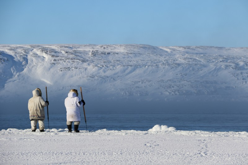 A young and an experienced hunter observe wildlife together at a polynya. (Photo Courtesy of the Arctic Eider Society)
