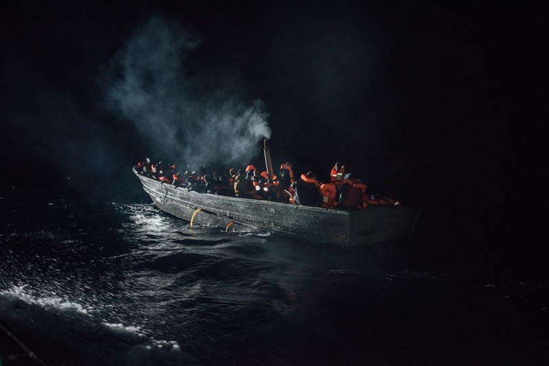 Migrants and refugees in a small wooden boat drift precariously in the dark of night in the Mediterranean Sea. Rescue crews on MV Aquarius spotted the boat and brought all its passengers on board, December 28, 2016. (Kevin McElvaney/MSF)