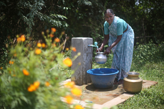 Woman collecting water in Pillayarkuppam village. (Water.org)