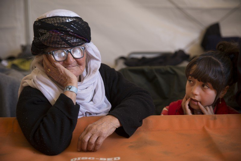 "Shereen (left), an 85 year-old Yazidi grandmother, escaped the ISIS onslaught of Yazidi villages in Shengal, Iraq. Here, she waits in a tent at Idomeni camp, before the camp was closed in May. On her right is a young Syrian refugee living in the same tent. One of Shereen's two grown sons is in Germany, and the other is in Sweden. Her nephew said he and his family helped bring her to Europe. ""We carried her on our back during parts of the journey,"" he said. Yazidis are leaving Iraq en masse. ""We can't live with the Muslims, it's not safe for Yazidi people,"" he explained. (Jodi Hilton)"