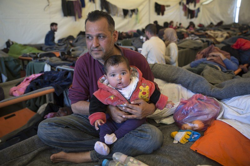 "Moayad Saad, a civil servant from Baghdad, Iraq, with his seven-month-old daughter Zehraa. ""We are always together,"" he said. Months earlier, when his family was trying to cross from Turkey to Greece, chaos broke out as people scrambled to board a rubber boat. He grabbed his baby daughter to protect her, but in the mayhem, the two of them never made it into the boat. It took him a month to get on another boat, since Turkish police kept stopping refugee boats from leaving. Meanwhile, Moayad's wife and four older children made it to Sweden. He and his infant daughter arrived in Idomeni after the border crossing into Macedonia closed. Their family reunification process can't begin until his wife receives refugee status, which is not guaranteed for Iraqis. ""I finally decided to leave [Iraq] after someone tried to break into my house and kidnap my wife and children,"" explained Moayad. He had been kidnapped once before and held for ransom. Kidnappings and violence are common in Baghdad these days, he said. (Jodi Hilton)"