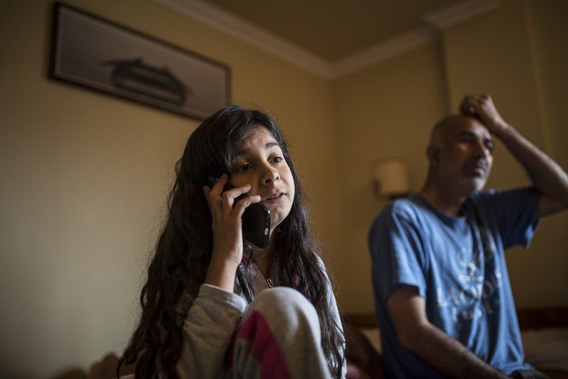 "Zeyneb Omer, a 13-year-old Syrian girl from Aleppo, speaks with her mother over Skype, as her father sits nearby. She hasn't seen her mother for more than eight months, and she's stranded in Greece with her father and younger sister. Her father Ziyad was a shoemaker in Syria. He explained, ""We heard that when women go to Europe, they are taken better care of,"" so the family decided to send Zeyneb's mother and younger brother ahead last year. They reached the Netherlands, but the reunification procedure can't even start until Zeyneb's mother is granted asylum status, which could take another four months. (Jodi Hilton)"