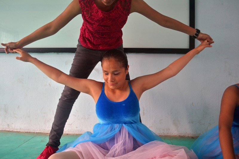 Nieva guides Pati's arms in a last-minute stretch before the group is called out for their first dance at La Rosa School in Chiapas, southern Mexico. (Eva Clifford)