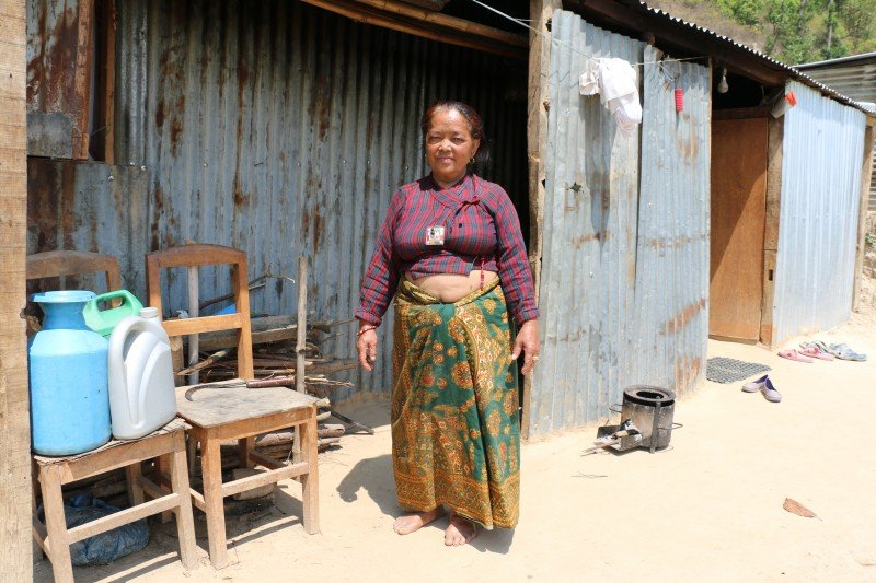 Tamang stands outside the flimsy tin shack she built after her house crumbled in a 7.8-magnitude earthquake last year. (Sonia Narang)