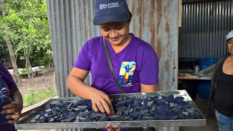 Romero Community president Carmen Acevedo holds a tray of indigo chips. In an example of the entrepreneurship that thrives in the community, women plant, harvest and process indigo plants before crushing them into powder to make a dye that they use to decorate products to sell. (Christine Bolaños)